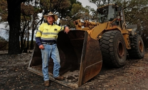 Waroona Farmer Peter Stacey with the damaged front end loader that he used to fight the fire along Coronation Rd. Picture: Michael Wilson, The West Australian.